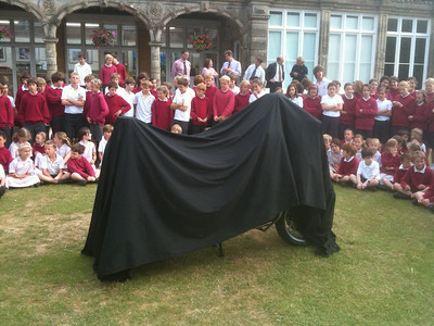 Freewheelers new motorcycle hidden under a black sheet is surrounded by pupils on the school lawns